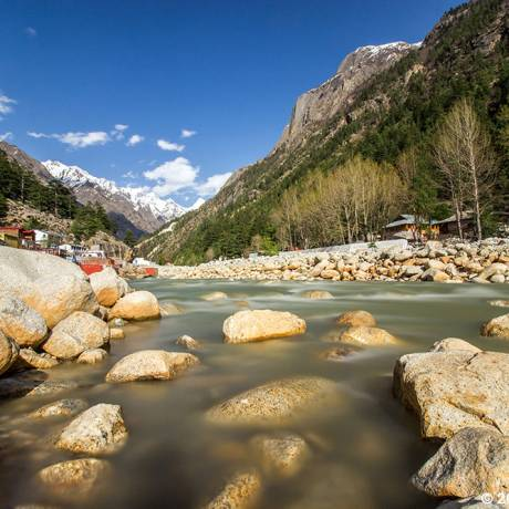 Ganga river flowing through the Gangotri(the origin of the river Ganga) and temples situated on the bank of Ganga river.