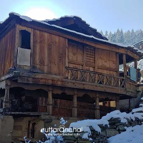 An old wooden house of Sankri village and snowy streets.